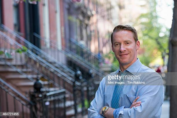 A man in a blue shirt and blue tie with arms folded, standing on the sidewalk outside a townhouse.