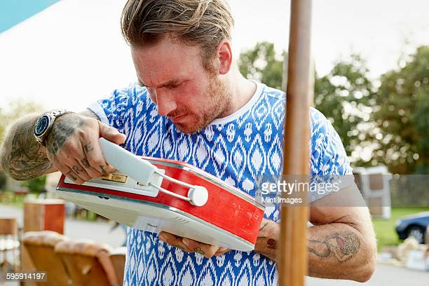 A man in a blue shirt with tattooed forearms, looking at a red vintage radio at a flea market.