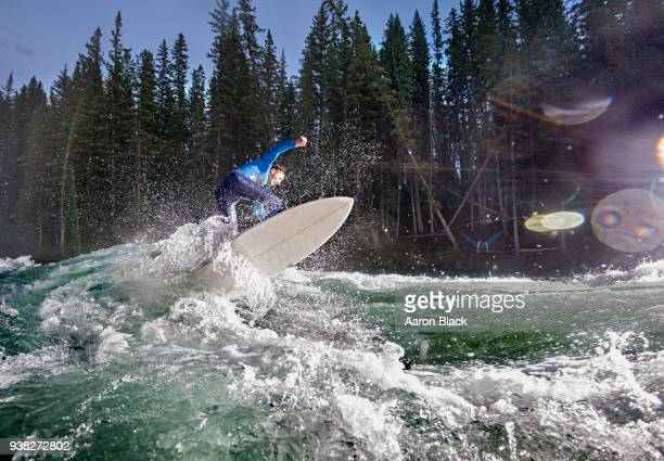 man in a blue wetsuit lit with flash at twilight jumping a surfboard over a turquoise wave in the middle of a river. - kananaskis stock-fotos und bilder