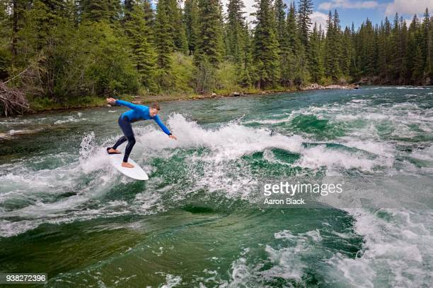 man in a blue wetsuit standing on surfboard surfing a turquoise wave in the middle of a river. - kananaskis country stock pictures, royalty-free photos & images