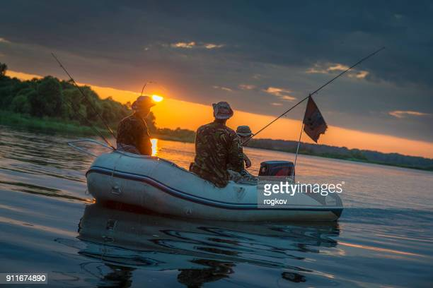 man in a boat at sunset fish. - pike fish stock pictures, royalty-free photos & images
