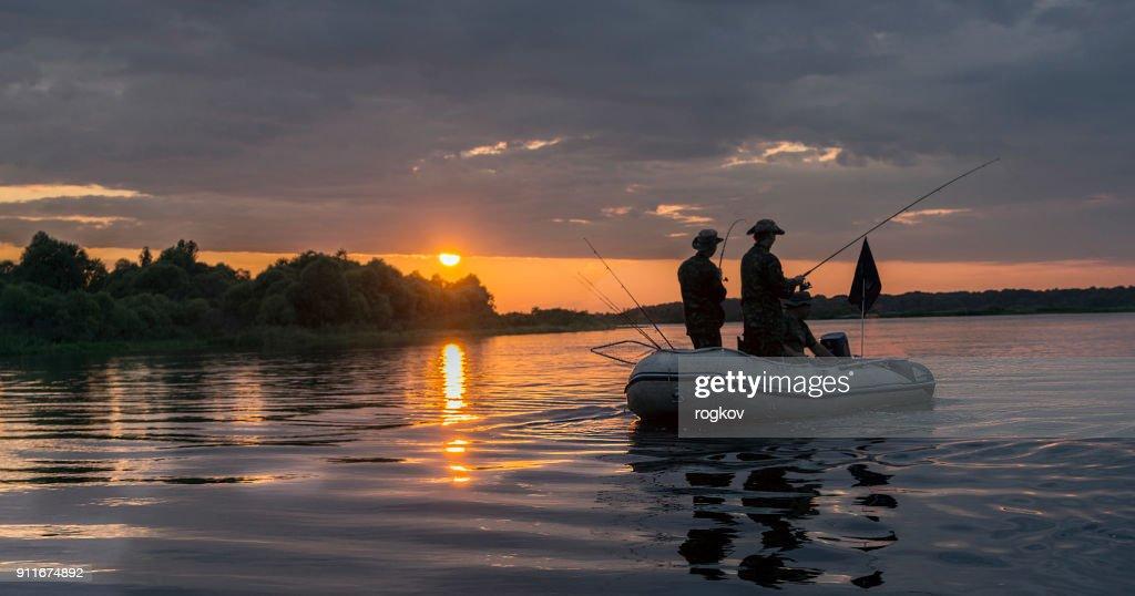 Homme dans un bateau au coucher du soleil poissons. : Photo
