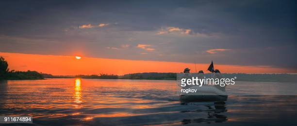 man in a boat at sunset fish. - bass fishing stock pictures, royalty-free photos & images