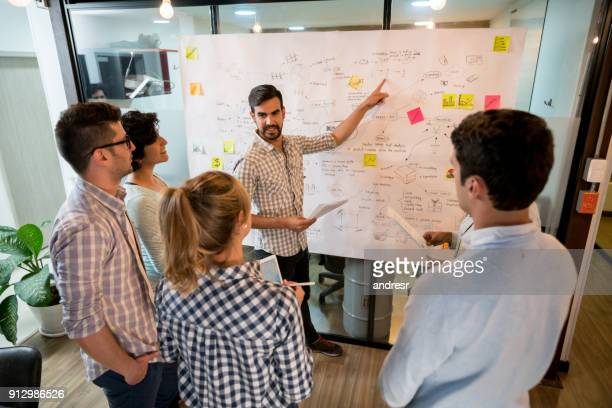 man in a business meeting at the office pointing at a business plan - business plan stock pictures, royalty-free photos & images