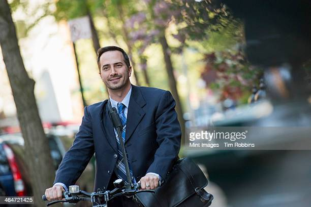 A man in a business suit, outdoors in a park. Sitting on a bicycle, with a cycle helmet in his hands.