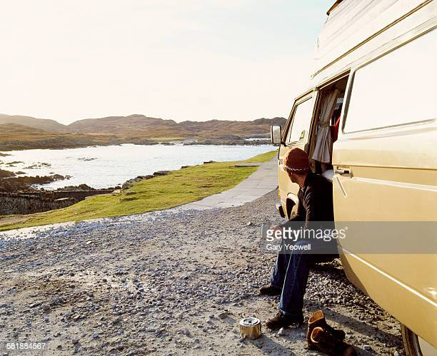 Man in a camper van looking out to sea