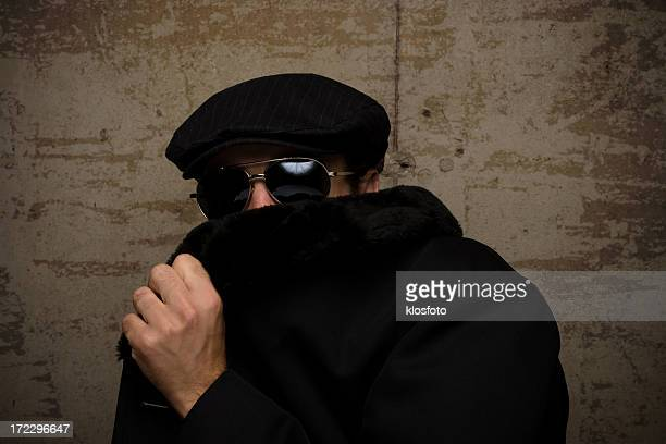 A man in a cap and dark glasses hides his face with his coat