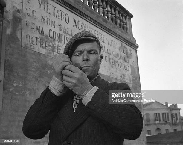 A man in a cap lights his pipe Comacchio Italy 1949 The faded sign on the wall behind him warms of the penalties of eels poaching