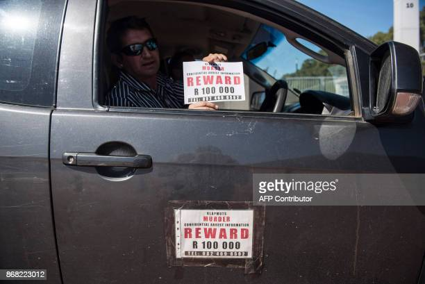 A man in a car holds a sign during a demonstration by South African farmers farm workers at the Green Point stadium to protest against farmer murders...