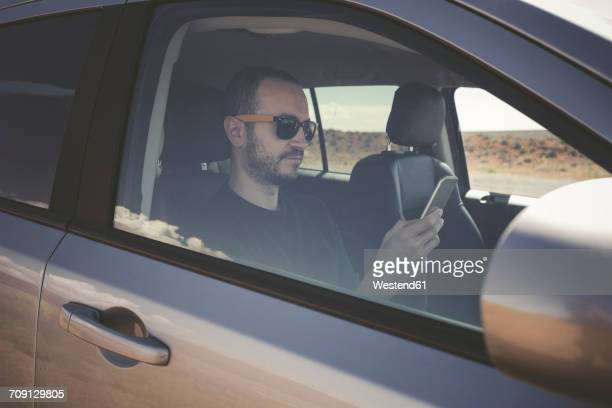 man in a car with smartphone - independence stock pictures, royalty-free photos & images