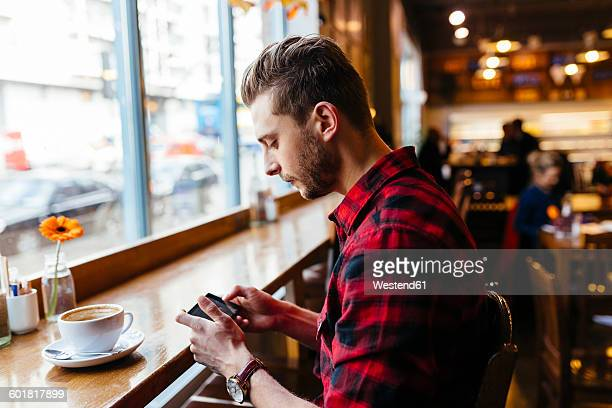 Man in a coffee shop looking at cell phone