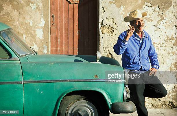 Man in a Cowboy Hat, Holding a Cigar and Smiling, Stands By a Parked Car in Havana, Cuba
