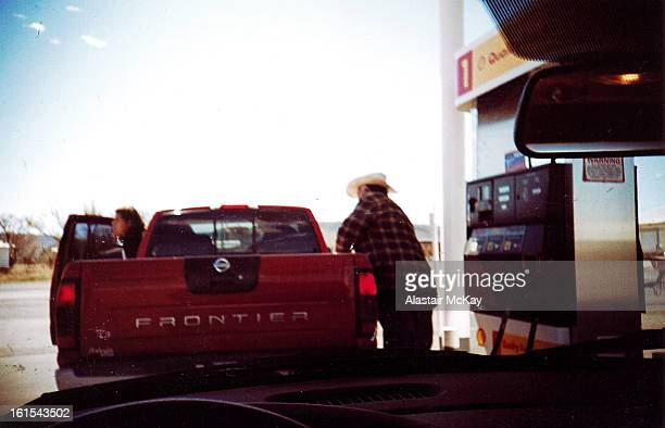 Man in a cowboy hat stops to fuel his pick-up truck at a gas staion in West Texas .