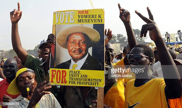 A man in a crowd of supporters holds up a sign portraying the face of Uganda's incumbent president Yoweri Museveni on February 16 2011 during...