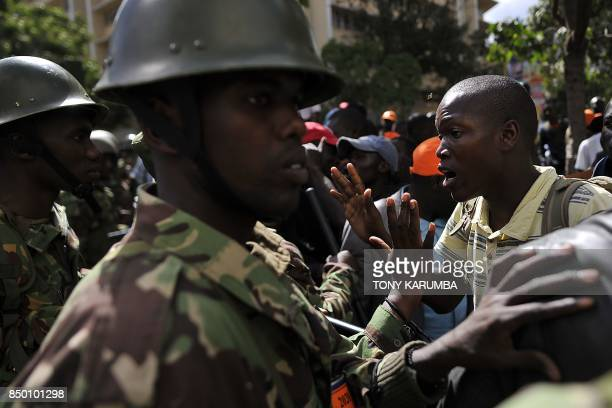 A man in a crowd of supporters of Kenya's main opposition National Super Alliance presidential flagbearer Raila Odinga argues with police officers...