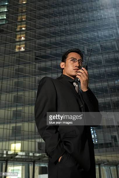 A man in a dark suit communicates on a two-way radio transceiver.