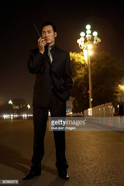 A man in a dark suit stands alongside a busy street, communicates on a two-way radio transceiver.