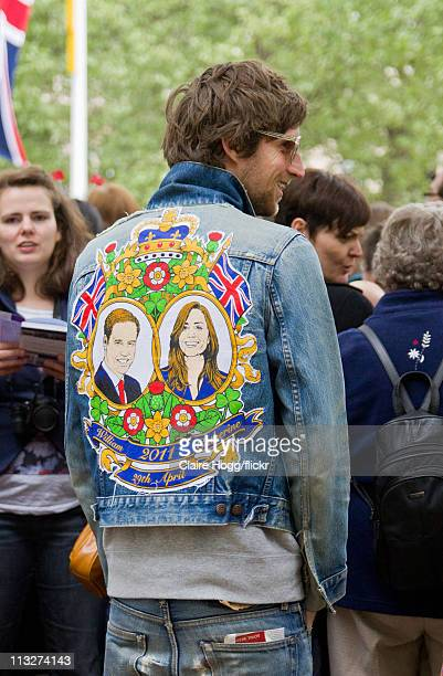 A man in a denim jacket with a commemorative William and Kate Middleton graphic on the back watches the Royal Wedding parade on The Mall during the...