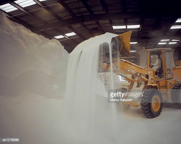 Man in a Digger Bulk Handling Chemicals in a Warehouse at Immingham Port, Humberside, UK