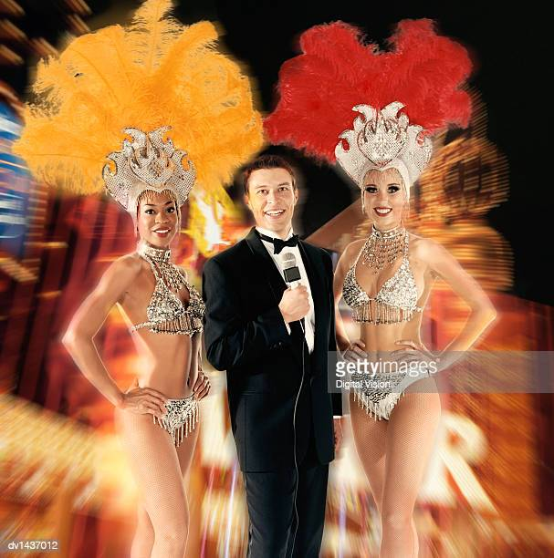 man in a dinner jacket holding a microphone stands between two chorus girls, against a blurred composite background - tocado de fiesta accesorio personal fotografías e imágenes de stock