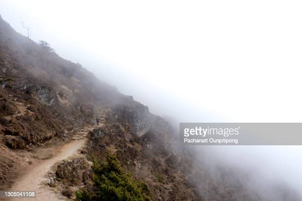 a man in a distance hiking on the mountain with a heavy mist in namche bazaar - solu khumbu stock pictures, royalty-free photos & images