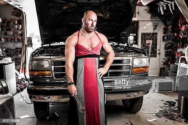a man in a dress repairing a truck - transvestite stock photos and pictures