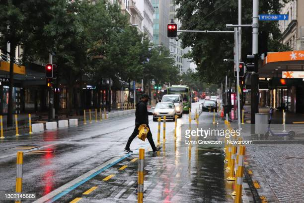 Man in a face mask crosses Queen Street in the early morning rain on February 15, 2021 in Auckland, New Zealand. Auckland is in alert level 3...