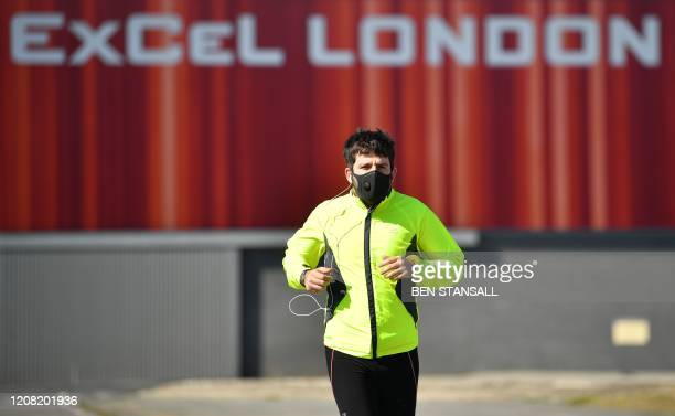 A man in a face mask jogs past the ExCeL London exhibition centre in London on March 25 2020 that the government announced will be converted into a...