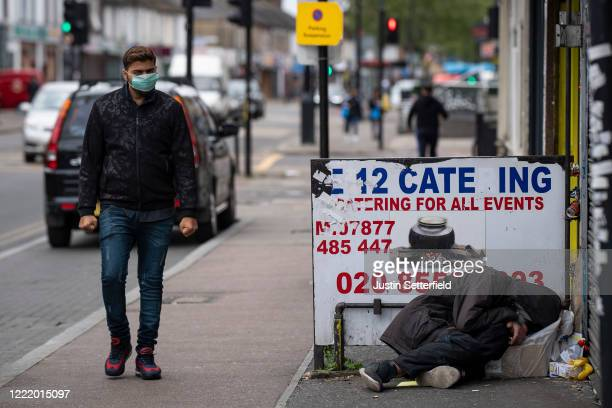 Man in a face mask walks past a homeless man sleeping on the streets in Ilford on April 30, 2020 in London, England. British Prime Minister Boris...
