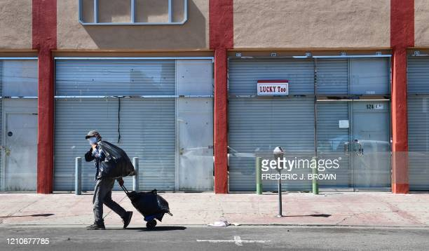 TOPSHOT A man in a face mask walks past closed shopfronts in the Fashion District in Downtown Los Angeles California on April 22 amid the novel...