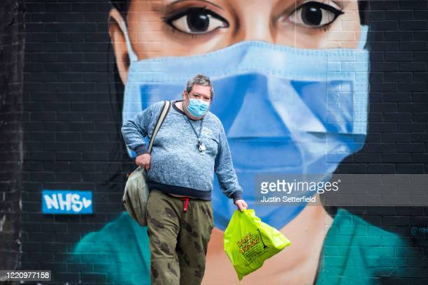 Man in a face mask walks past graffiti by artist Graffiti Life in East London on April 25, 2020 in London, England. The British government has...