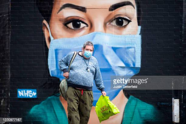 A man in a face mask walks past graffiti by artist Graffiti Life in East London on April 25 2020 in London England The British government has...