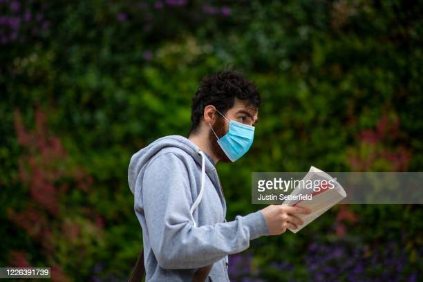 Man in a face mask walks through Canary Wharf reading a book on May 22, 2020 in London, England. The British government has started easing the...