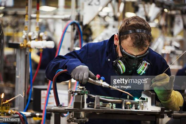 A man in a facemask with breathing filters, a skilled factory worker welding arts of a bicycle in a factory.