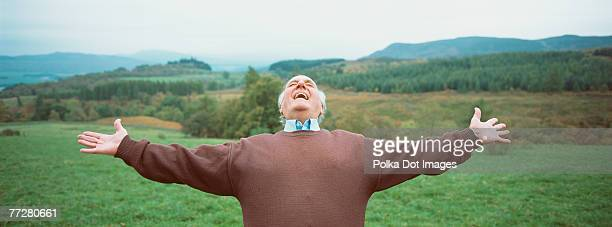Man in a field with his arms outstretched