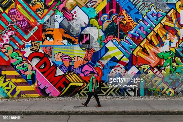 A Man In A Green Shirt Walking Past A Colorful Graffiti