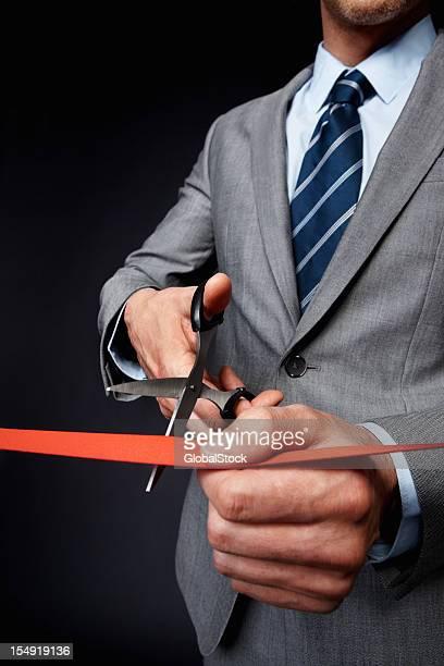 Man in a grey suit cutting an orange ribbon