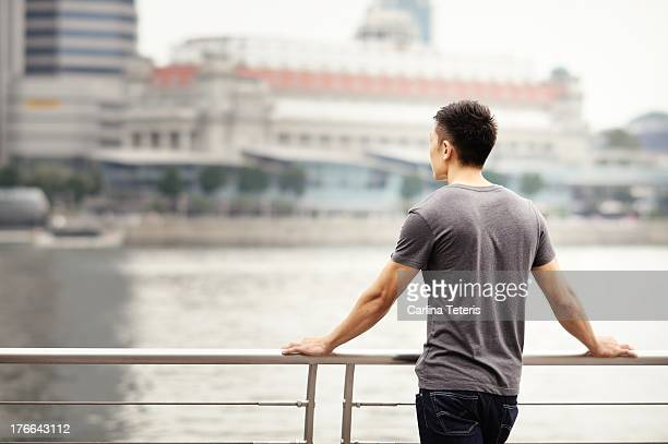A man in a grey tshirt looks out across Marina Bay