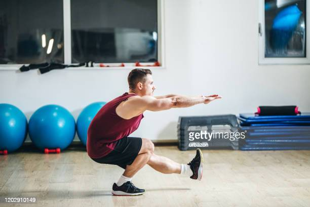 man in a gym - crouching stock pictures, royalty-free photos & images