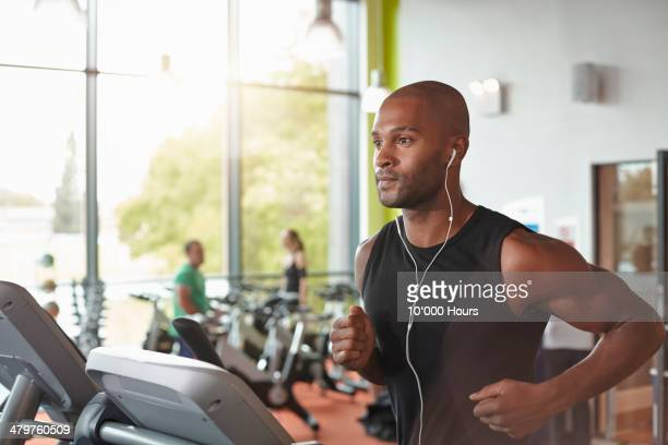 Man in a gym running on a treadmill.