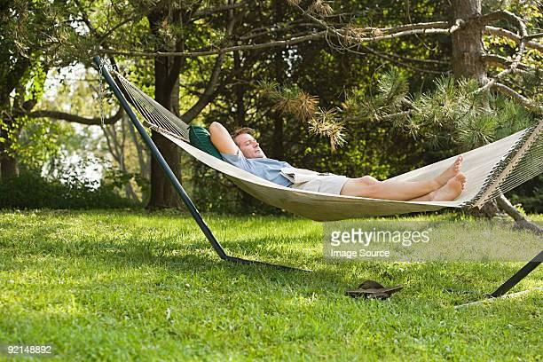 man in a hammock - hamac photos et images de collection