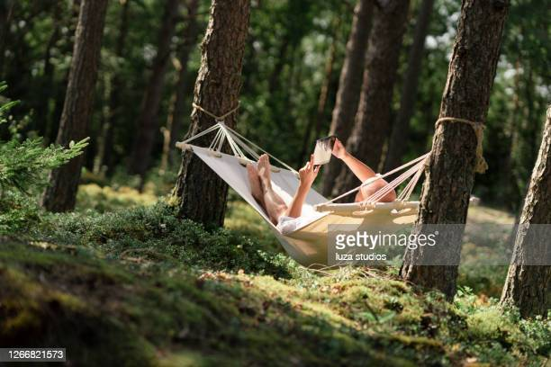 man in a hammock reading a book on a tablet - sweden stock pictures, royalty-free photos & images