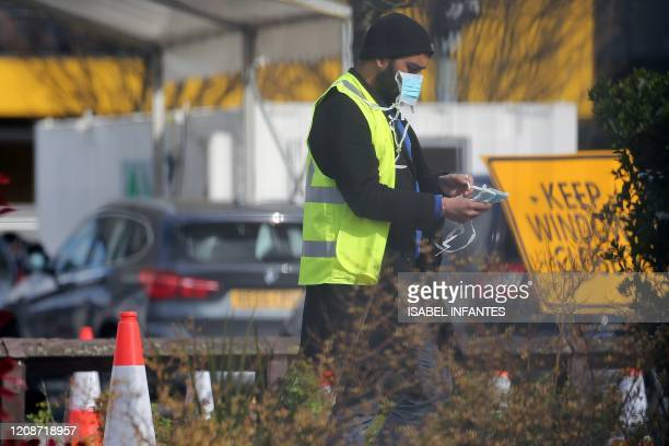 Man in a high-vis jacket holds face masks as NHS workers wait in the cars to be tested for COVID-19, at a drive-in facility set up in the car park of...
