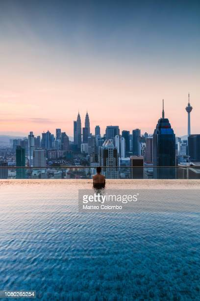 man in a infinity pool with kuala lumpur skyline, malaysia - kuala lumpur stock pictures, royalty-free photos & images