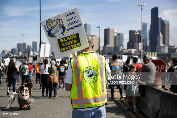 A man in a International Longshore and Warehouse Union vest holds a Black Lives Matter sign during a Juneteenth Shutdown of All Pacific Coast Ports...