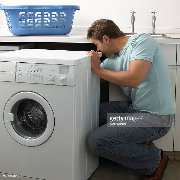 Man in a Kitchen Repairing a Washing Machine