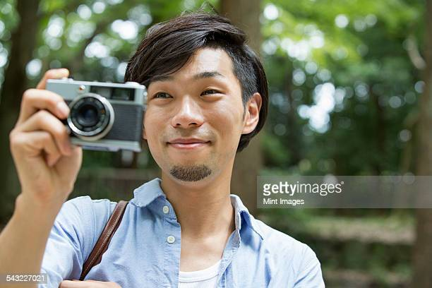 A man in a Kyoto park holding a camera, taking a picture.