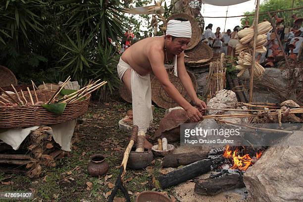 A man in a loincloth handle meat brochettes animal A market prehispanic dances and offerings to the goddess Ixchel were the first events of the...