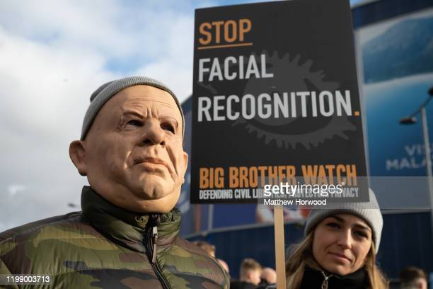 A man in a mask attends a protest against the use of police facial recognition cameras at the Cardiff City Stadium for the Cardiff City v Swansea...