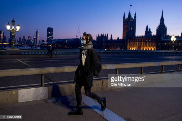A man in a mask crosses Westminster Brdge at the end of the first day of the Corona Virus Covid19 Lockdown on March 24 2020 in London British Prime...